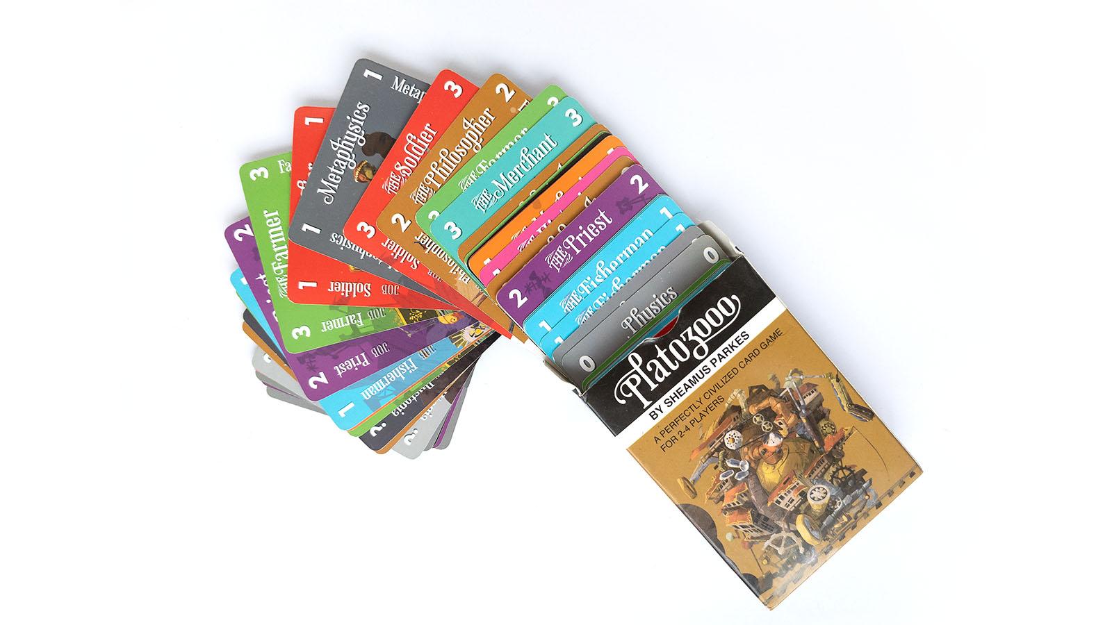 """Aufmacherbild das Packungsgestaltung des Spiels """"Plato 3000"""" von Cambridge Games Factory zeigt, sowie einige Karten die aus der Packung hervorschauen."""